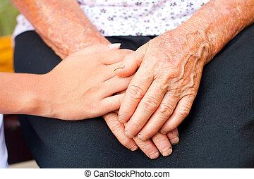 Caring - Young hands between elderly ones.