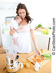 Caring young mother preparing vegetables for her baby in the kitchen at home