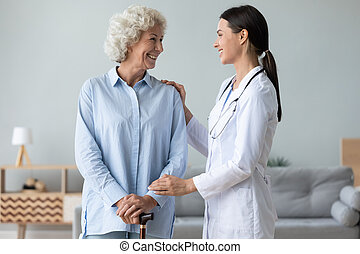 Caring young nurse helping old lady patient