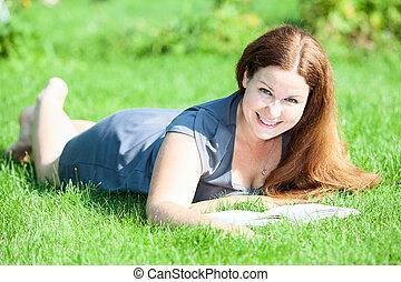 carino, donna sorridente, dire bugie, su, erba verde, con, libro, in, mani