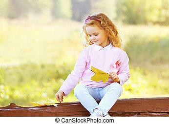 carino, piccola ragazza, bambino, con, giallo, acero, mette foglie, in, giorno autunno