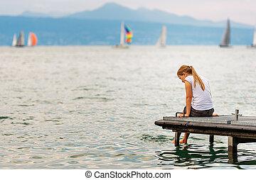carino, poco, capretto, ragazza, riposare, vicino, il, lago, seduta, su, banchina, acqua schizza, con, lei, piedi, vista posteriore
