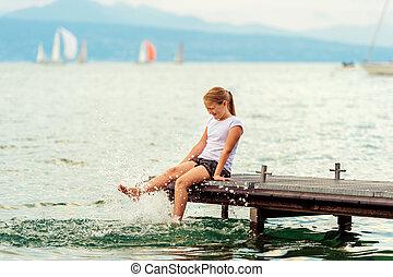 carino, poco, capretto, ragazza, riposare, vicino, il, lago, seduta, su, banchina, acqua schizza, con, lei, piedi