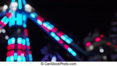 Carnival fair grounds at night. Defocused footage. Shot in...