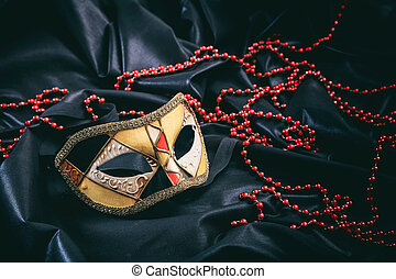 Carnival mask on black satin background