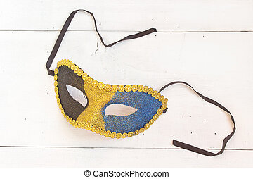 Carnival mask on white wooden background
