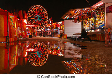 Carnival lights are reflecting in pools of water.