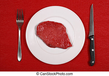 Raw meat on a dinner plate with knife and fork.