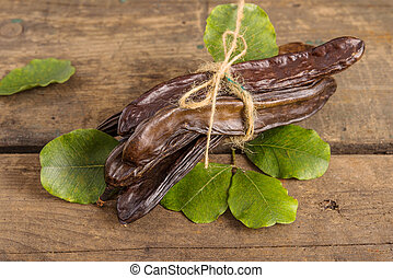 Carob, ceratonia siliqua - Raw fruits Carob on old wooden...