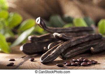 Carob Pods and Seeds on Wood with Leaves