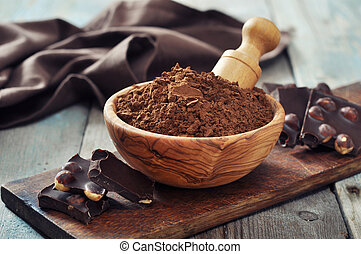 Carob powder in bowl with chocolate pieces on wooden...