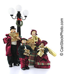 A family of four old-fashioned caroling figurines under a wreath-adorned light post. Isolated on white.