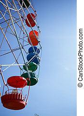 carousel ferris wheel on blue sky background