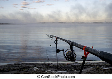 Carp fishing rod close-up with a coil on the background of water with rising thick fog. No body