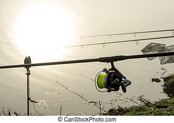 Carp fishing rod with a coil in the foreground and a bite alarm on the background of reflection in the water of the morning sun in the fog.