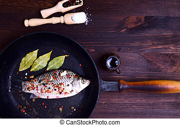 Carp in spices on a black cast-iron frying pan - Carp fish...