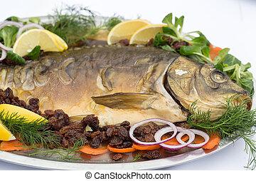 carp  with lemon, dill and raisins on plate