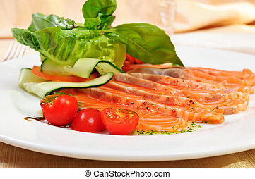 Carpaccio of salmon with cherry tomatoes in restaurant