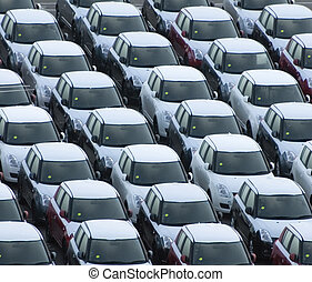 Rows of brand new cars and trucks parked and waiting for delivery