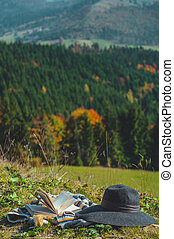 Carpathian alpine mountain. Pages of an open book, hat and thermo cup. Majestic landscape. Nature and education concept.