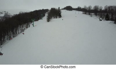 Carpathian ski resort from a height. Flight over mountains. Bird's eye view of people descending on skis.