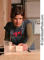 A female cabinetmaker rips a piece of pine on a tablesaw.