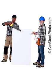 Carpenter and electrician with a blank board