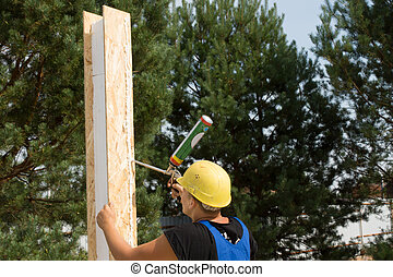 Carpenter applying wood glue to a panel