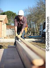 Carpenter arranging wooden beans on work-site