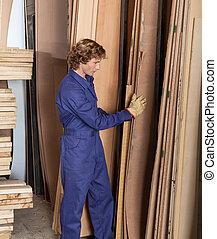 Carpenter Arranging Wooden Planks In Workshop