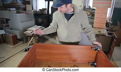 Carpenter assembling furniture in workshop