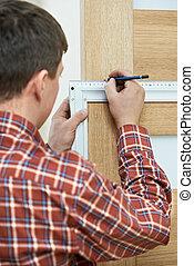 Male handyman carpenter at interior wood door lock installation with angle