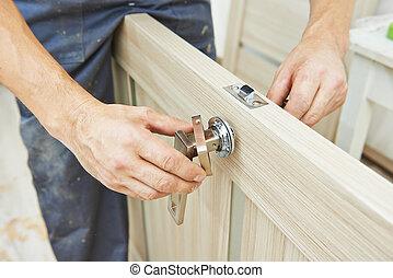 carpenter at door lock installation - Male handyman...