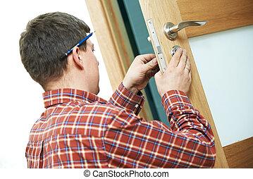 carpenter at door lock installation - Male handyman ...