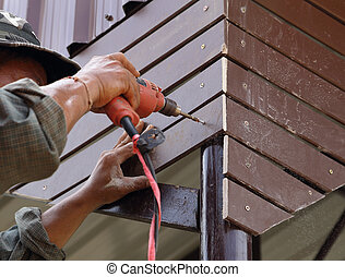 carpenter at lock installation with electric drill