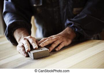 Carpenter at work - Professional carpenter sanding and...