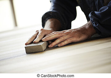 Carpenter at work - Professional carpenter sanding and...