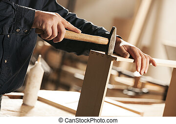 Carpenter at work - Carpenter hammering a piece of furniture...