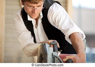 Carpenter at work with a circular saw