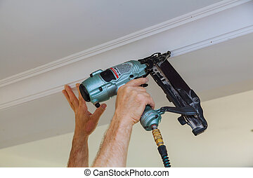 Carpenter brad using nail gun to Crown Moulding framing...