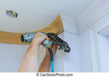 Carpenter brad using nail gun to Crown Moulding framing trim...
