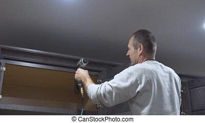 Carpenter brad using nail gun to Crown Moulding on kitchen cabinets framing trim