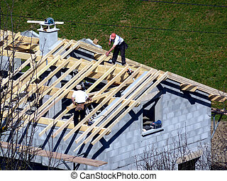 Carpenter building a roof of a house