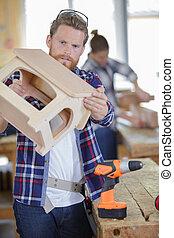 carpenter checking house model assemble