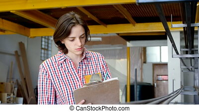 Carpenter checking material and writing on clipboard 4k - ...