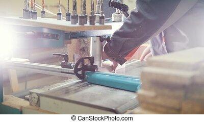Carpenter cut a wooden fragment on a furniture factory,...