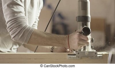 Carpenter cut wooden board by plunge router. Furniture....