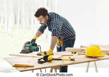 Carpenter cutting plank by circular saw