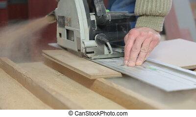 carpenter cutting wood panel circular saw