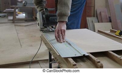 carpenter cutting wood panel
